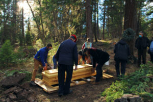 lowering unfinished wood casket into natural grave